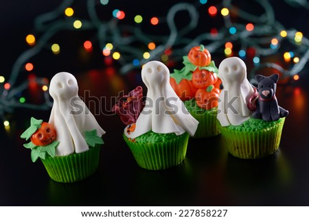 Halloween cupcakes decorated with sugar ghosts and pumpkins. Diagonal framing. - stock photo