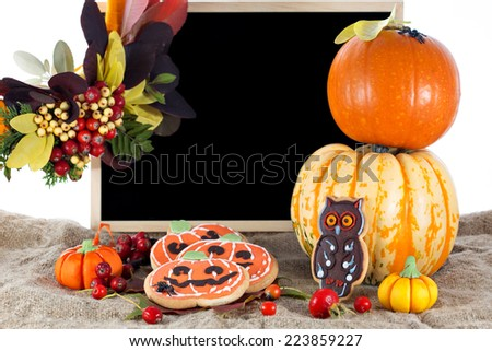 Halloween decorative cookies and pumpkins as popular American event party dessert idea. Blackboard on background for your text. Isolated on white background - stock photo