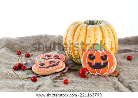 Halloween decorative cookies and pumpkins as popular American event party dessert idea. Isolated on white background - stock photo