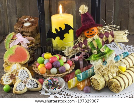 Halloween doll with treats, cookies, sweets and burning candle - stock photo