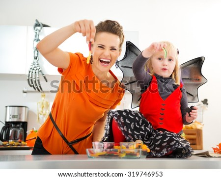Halloween dressed baby girl with young cheerful mother showing colorful gummy worm candies in decorated kitchen.  Halloween Candy is so good. Traditional autumn holiday - stock photo