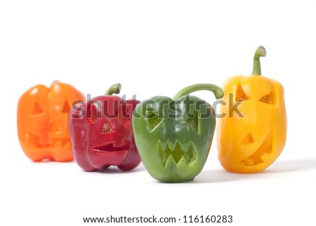 Halloween faces carved into orange, red, yellow and green capsicum vegetables instead of pumpkin forming special jack o lanterns. - stock photo