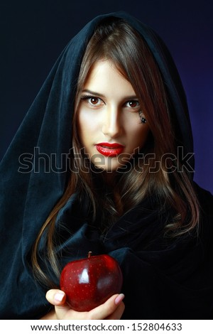 Halloween. Fashion portrait of witch or night vampire woman offering poisoned apple. Bright red lips - stock photo