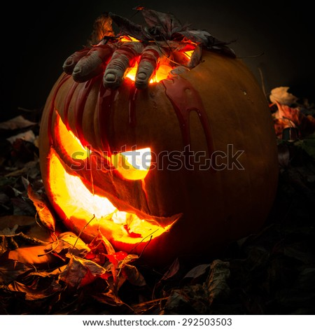 Halloween fear or scare: Carved halloween pumpkin with a bloody hand. The spooky and creepy fall tradition of Halloween - stock photo