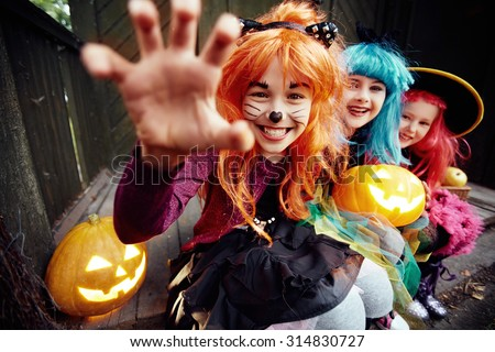 Halloween girl looking at camera with her hand in frightening gesture - stock photo