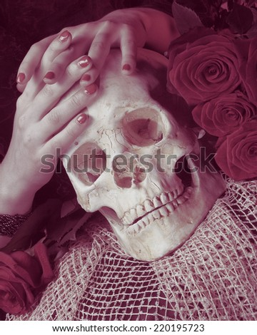 Halloween: Hands of young woman and skull - stock photo