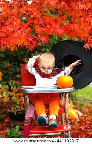 Halloween holiday. Girl throws a big black hat. little girl blonde in a black hat sitting at a table next to a pumpkin in the garden - stock photo