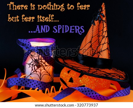 Halloween image for October 31st. Sparkly jack-o-lantern with colored light inside wearing witch hat with spider web. Orange and purple ribbon decoration. Spider votive. Black background with message - stock photo