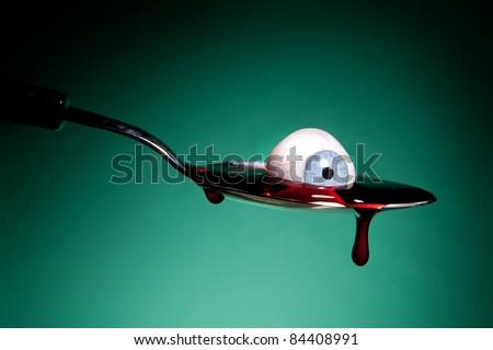 Halloween image of a bleeding glass eye in a metal spoon - stock photo