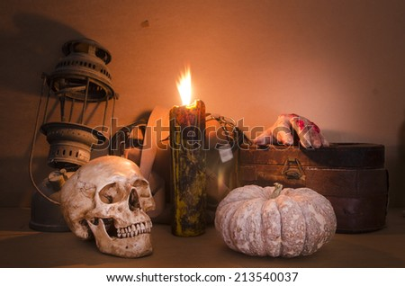 Halloween image with a burning candle on an ancient skull - stock photo