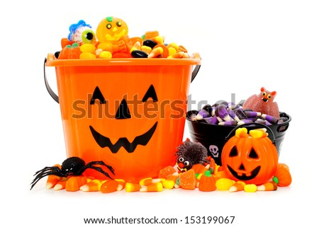 Halloween Jack o Lantern candy bowls with assorted candy over white - stock photo