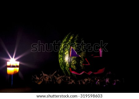 Halloween. Jack O' Lantern of watermelon on the black with leaves. - stock photo