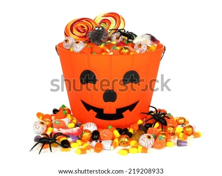 Halloween Jack o Lantern pail with pile of candy over white                                - stock photo
