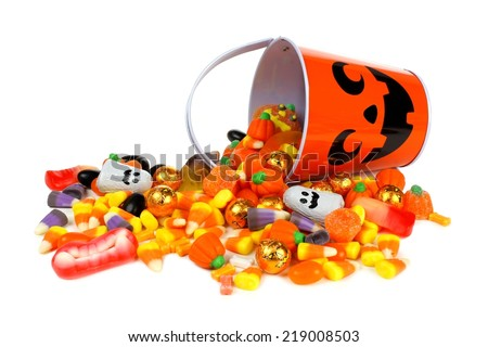 Halloween Jack o Lantern pail with spilling candy over white              - stock photo