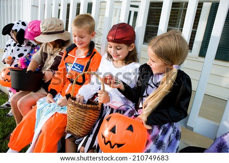 Halloween: Kids Sit On Porch And Look At Halloween Candy - stock photo