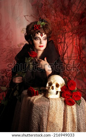 Halloween lady. Young woman in black with artistic visage and with rose in her hair - stock photo