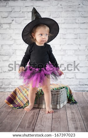Halloween little girl witch standing on a floor - stock photo