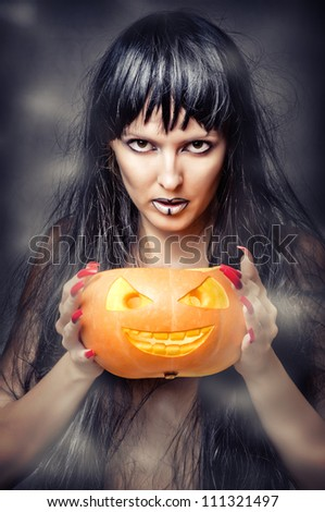 Halloween makeup. Sexy woman - Witch with long black hair and pumpkin smiling and look to shot - stock photo