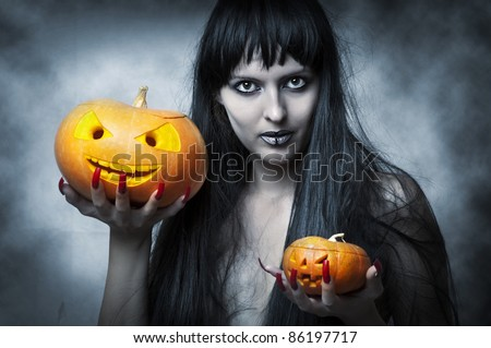 Halloween makeup. Sexy woman - Witch with long black hair and two pumpkins in hands smiling and look to shot - stock photo