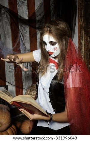 Halloween, mysticism, magic, mystery. Makeup in the style of Billy doll. A witch casts a spell over magic book - stock photo