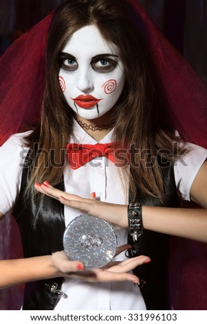 Halloween, mysticism, magic, mystery. Makeup in the style of Billy doll. A witch holding a magic transparent sphere. - stock photo