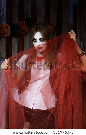 Halloween, mysticism, magic, mystery. Makeup in the style of Billy doll. The witch is hiding behind the red transparent cloth. - stock photo