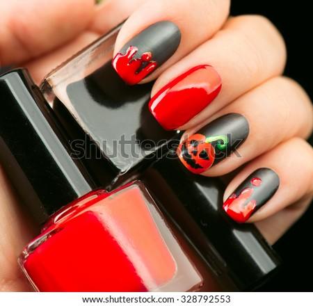 Halloween Nail art design. Nail Polish. Beauty hands. Trendy Stylish Colorful Nails and Nailpolish. Black matte nailpolish with blood drips and pumpkin - stock photo