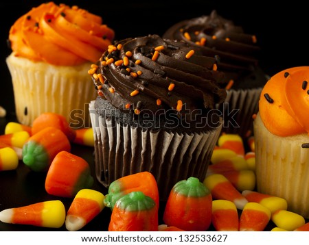 Halloween orange and black cupcakes with candy corn candies on black background. - stock photo