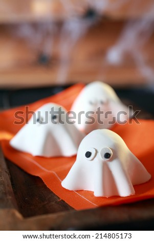 Halloween party decorations from folded pastry dough in the shape of scary little ghosts with big eyes on an orange napkin with copyspace for your greeting or invitation - stock photo