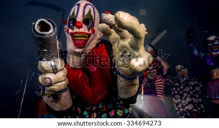 Halloween party scary clowns. The clown with a gun. - stock photo