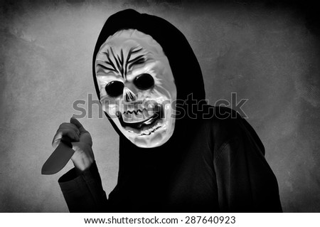 Halloween party. Woman in black with a plastic human skull mask holding a knife - stock photo