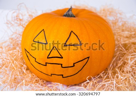 Halloween preparation concept - close up of funny pumpkin with face - stock photo
