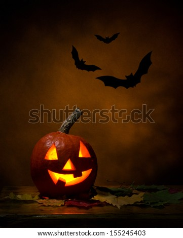 Halloween -  pumpkin and bats, maple leafs on wooden table, dark-brown background - stock photo