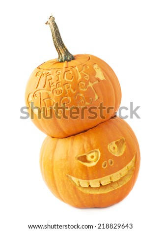 Halloween pumpkin composition with one Trick or treat pumpkin placed over the Jack-o'-lanterns pumpkin head, composition isolated over the white background - stock photo