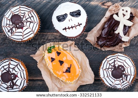 Halloween pumpkin cupcakes and cakes decorated with icing on old wooden background. Halloween sweets background. Top view - stock photo