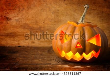 Halloween pumpkin head jack lantern on wooden background - stock photo