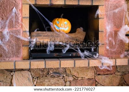 Halloween pumpkin in a fireplace - stock photo