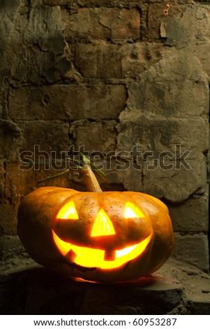halloween pumpkin in night on old brick wall - stock photo
