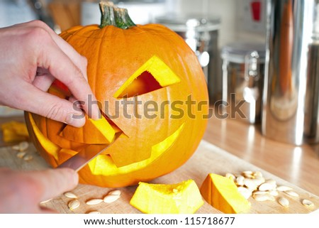 Halloween pumpkin Jack O'Lantern being carved for Halloween - stock photo