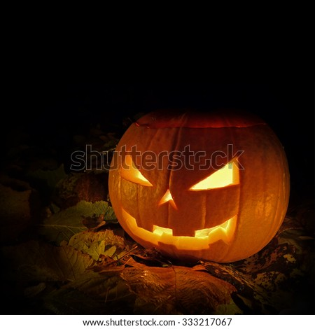 Halloween Pumpkin Jack-O'-Lantern on fallen Autumn leaves outside with copy space - stock photo
