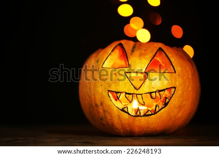 Halloween Pumpkin on table on dark color background with multicolor lights - stock photo