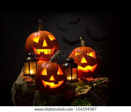 halloween pumpkins and bat with lanterns on dark background - stock photo