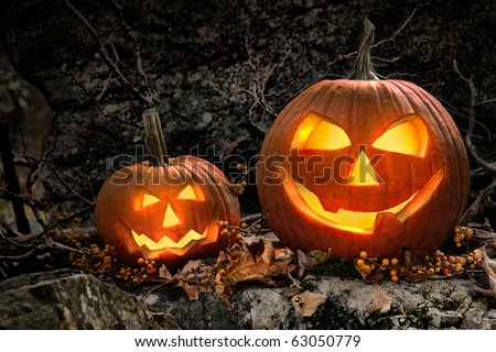 Halloween pumpkins on rocks in a forest at night - stock photo