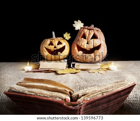 Halloween pumpkins reading old book at black background - stock photo