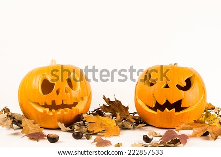 Halloween pumpkins with autumn leaves isolated on a white background with copy space for text. Scary faces concept - stock photo
