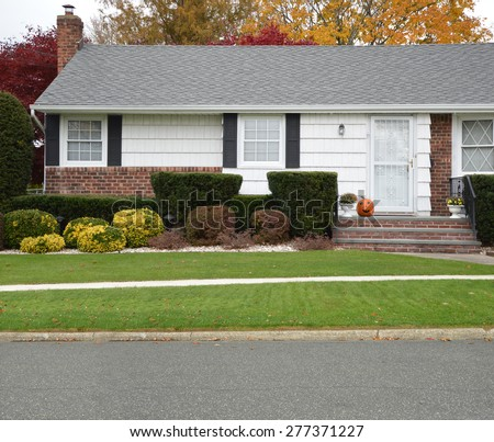 Halloween Season Close up of Ranch style Home Autumn Day Pumpkin Smile on Stoop Residential Neighborhood USA - stock photo