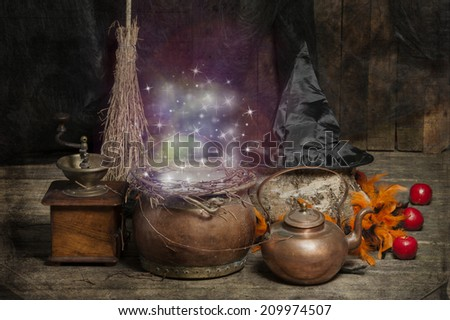 Halloween still live with hat, coffee mill, broom and cauldron - stock photo