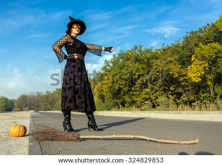 Halloween Theme Dressed Lady Hitchhiking on Paved Road Witch in Black Dress Hat and High Heels Boots Run Out of Fuel for Her Broom and Trying to Catch Up Another Mode of Transportation - stock photo