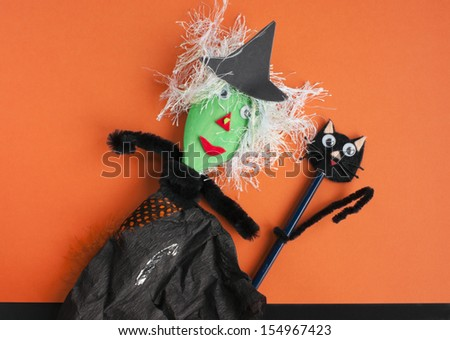 Halloween toys. Witch made of a wooden spoon, tissue paper and pipe cleaners and a cat made of an old pencil and pipe cleaners. Concept for Halloween craft and fun with children. - stock photo