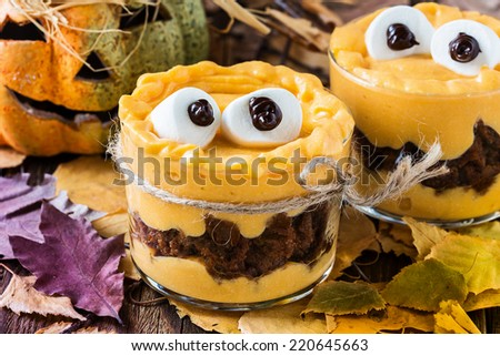 Halloween treats, little monster dessert with chocolate cookies and orange pumpkin  mascarpone cream  topped with big marshmallow eyes - stock photo